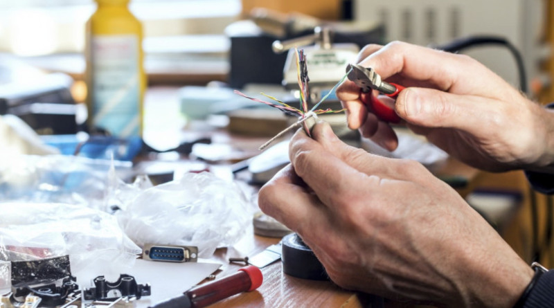 Man's hands holding cable with colorful wires and pliers over the working table in order to strip the wire for soldering.